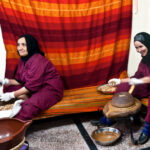 One woman cracking the Argan nuts, and The other grinding
