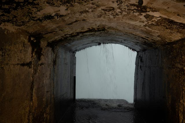 in tunnel under waterfall