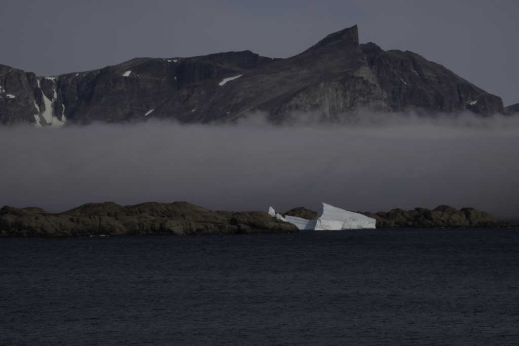 Small iceberg with opposite rock formation in background
